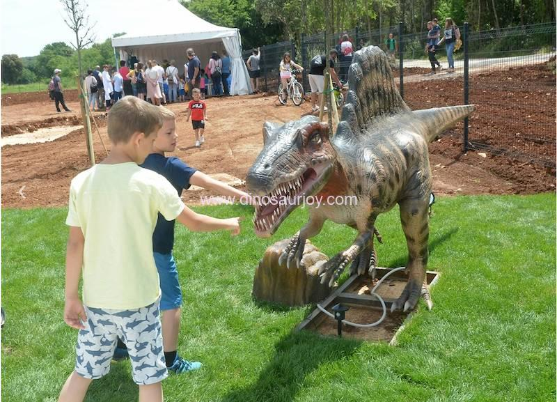 two kids playing with a fiberglass dinosaur