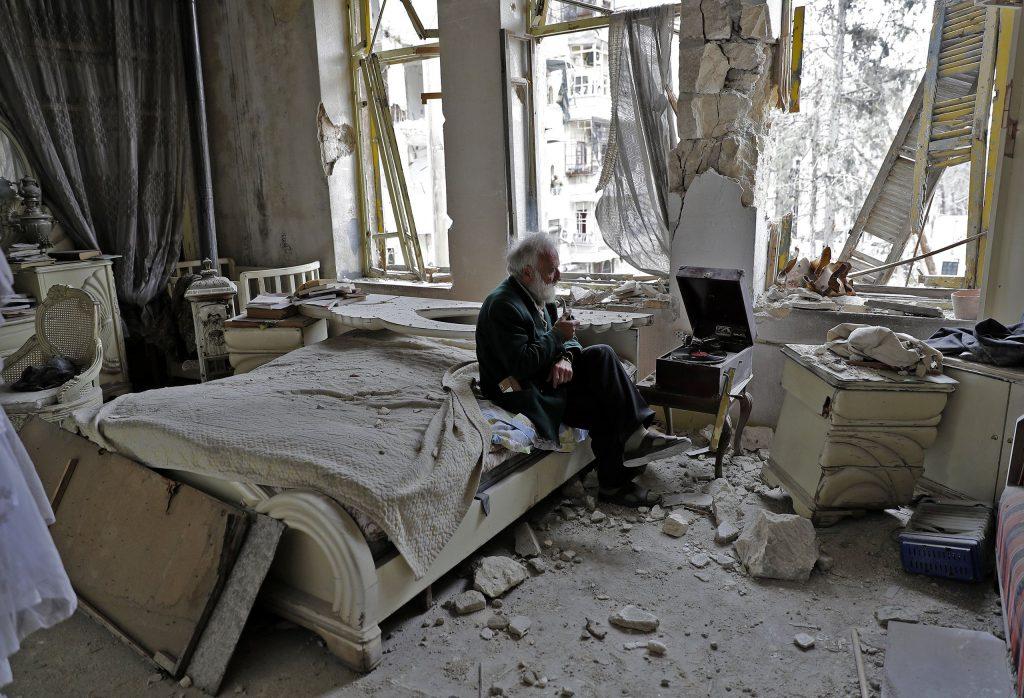 2017年,叙利亚阿勒颇,70岁的阿布·奥马尔(Abu Omar)在被毁的卧室里抽着烟斗听音乐