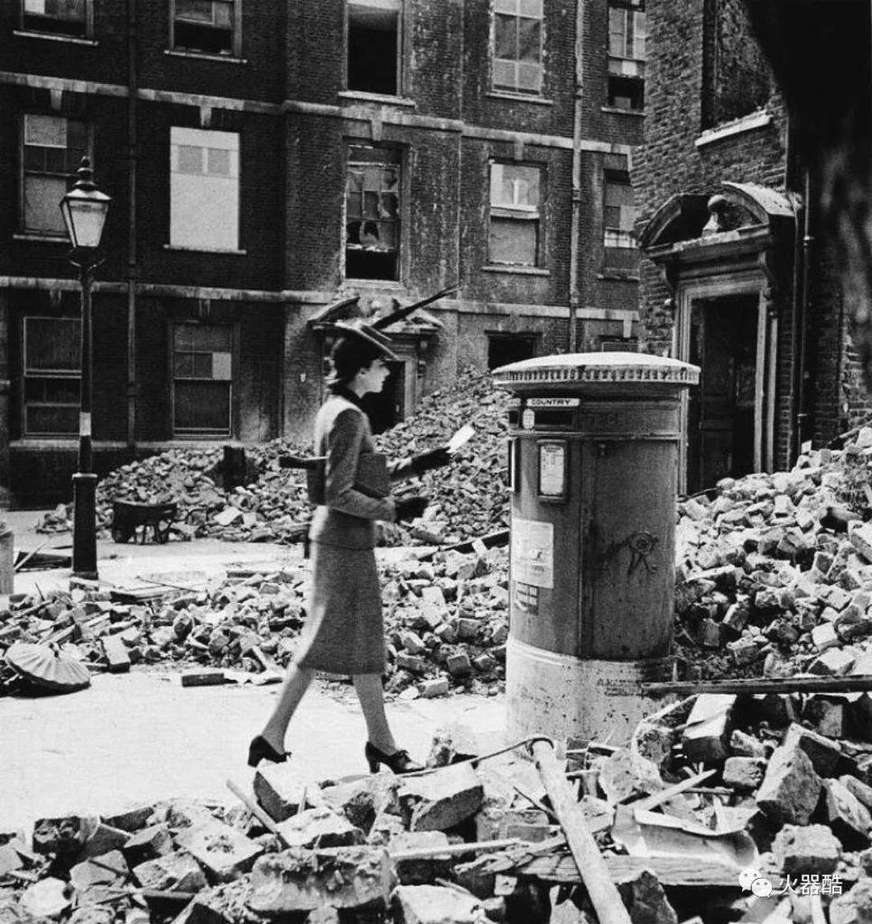 1940年,在德军轰炸考文垂后, 一位优雅的女士踩着废墟, 前往邮桶寄一封不知何时能被收到的信