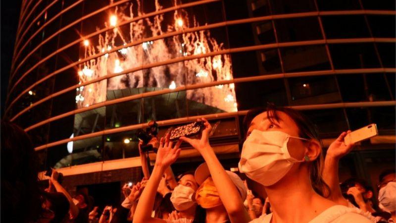 观看东京奥运开幕式烟花的民众