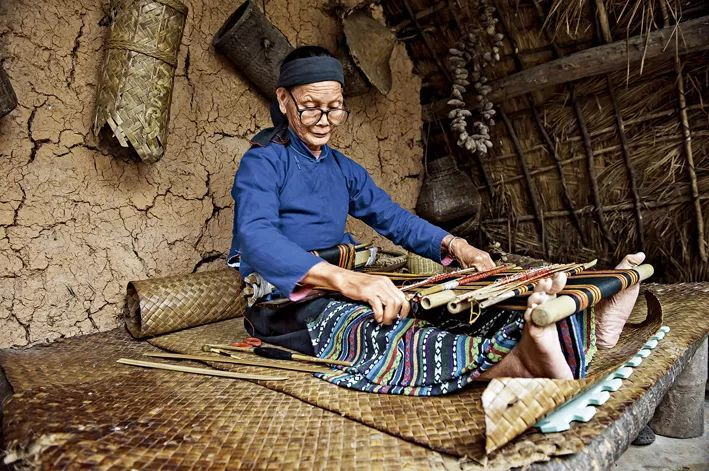 海南省黎族老太太编织传统的毯织品。